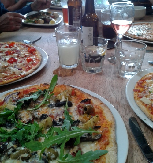 The pizzas are so big they barely fit on the table let alone the plates.
